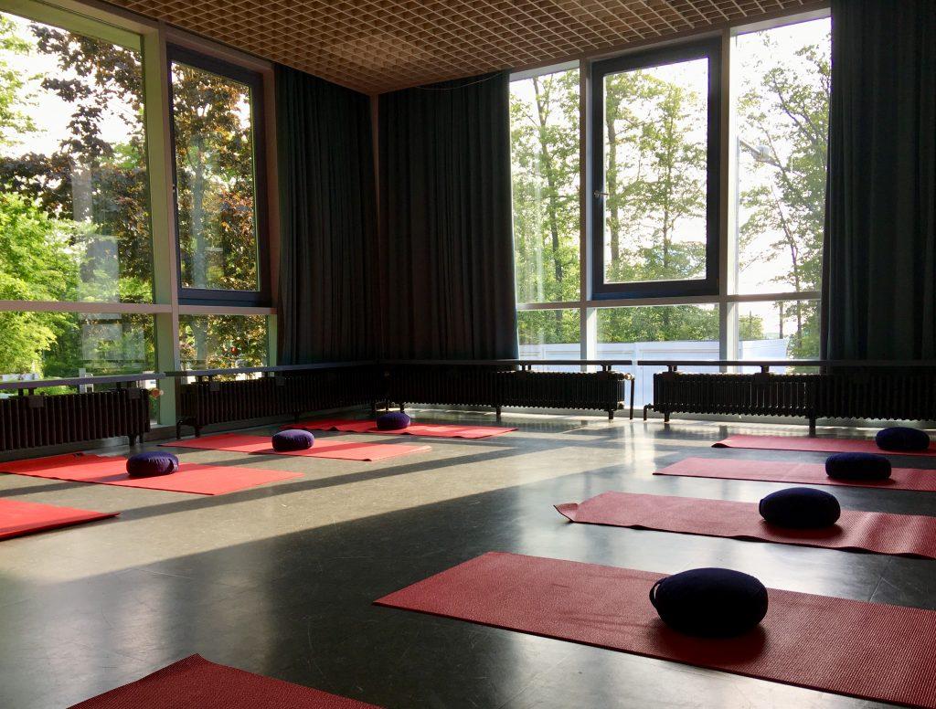 Bild des Gemeinderaums auf dem Lerchenberg mit Yogamatten und Kissen.